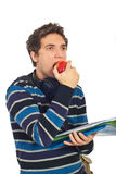 Student guy eating an apple. And looking away isolated on white background Stock Photo