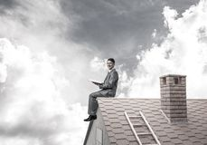 Student guy in suit on brick house roof reading book. Young businessman in suit sitting on house with red book in hands stock images