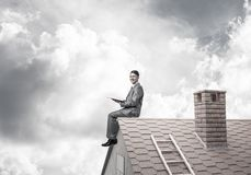 Student guy in suit on brick house roof reading book. Young businessman in suit sitting on house with red book in hands royalty free stock photography