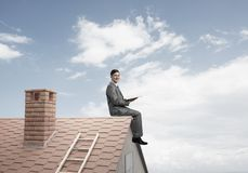 Student guy in suit on brick house roof reading book. Young businessman in suit sitting on house with red book in hands royalty free stock photos
