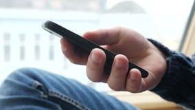 Student Hand Using Smartphone on Windowsill