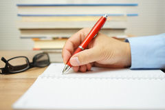 Student hand is writing in notepad with bunch of books in backgr Royalty Free Stock Photography