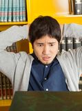 Student With Hands Behind Head Looking At Books In. Worried young male student with hands behind head looking at books in college library Stock Images