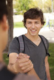 Student handshake. Happy young student giving a handshake to his classmate (selective focus Stock Photography