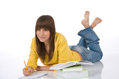 Student - Happy female teenager write homework. With book on white background Royalty Free Stock Photos