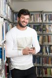 Handsome College Student Using Mobile Phone In Library. Student Happy With Online Learning Study By E-Learning Content Technology With Mobile Phone Royalty Free Stock Images