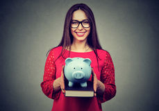 Student, happy woman, holding books and piggy bank in hands stock photo