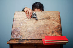 Student has brought a gun to school. Student is hiding his face behind an old school desk with a gun in his hand Royalty Free Stock Photography