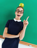 Student having good idea, pointing finger up and balancing an apple on her head Royalty Free Stock Images