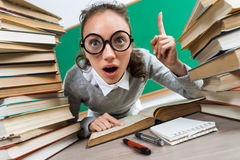 Student having good idea, pointing finger up. Photo of astonished young girl wearing glasses around books. Education concept royalty free stock image