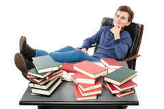 Student having a rest with the legs on the desk, daydreaming amo Royalty Free Stock Images