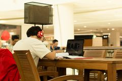 Student with headphones on doing home work in cafe with laptop Stock Photo