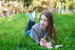 Student with headphones lying on grass Stock Photography