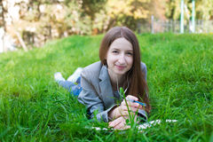 Student with headphones lying on grass Stock Photos