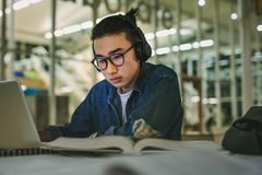 Student with headphones studying on the laptop at library royalty free stock photo