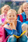 Student and her friends. Primary school female student and her friends sitting with backpacks Stock Images