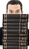 Student hidden behind a pile of books Stock Image
