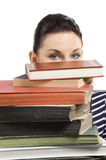 Student hiding. Close up portrait of young and cute brunette student hiding her face behind a pile of books Stock Images