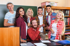 Student High School Group Laughing With Professor Sitting At Desk, Smiling Young People University Classroom. Over Chalkboard Stock Photo