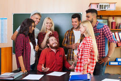 Student High School Group Laughing With Professor Sitting At Desk, Young People Teacher Discuss Communicate. University Classroom Royalty Free Stock Images