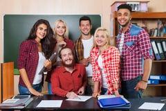 Student High School Group met Professor Sitting At Desk, het Glimlachen Jongeren Universitair Klaslokaal stock foto