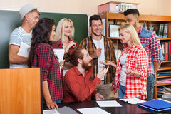 Student High School Group Talking With Professor Sitting At Desk, Young People Teacher Discuss Communicate. University Classroom Stock Photography
