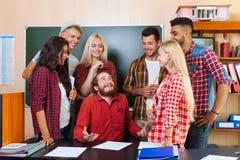 Student Highschool Group, das mit Professor Sitting At Desk, junge Leute-Lehrer Discuss Communicate lacht lizenzfreie stockbilder