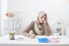 Student with hijab tired of doing homework. Asian female student with hijab tired of doing homework royalty free stock image