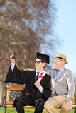Student and his proud father taking selfie in park. Student and his proud father taking selfie outdoors Royalty Free Stock Photography