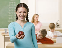 Student holding apple. Student holds an apple towards the camera while standing in a classroom Stock Photo