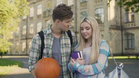 Student holding ball, flirting with pretty girl near university, asking for date. Stock footage stock video