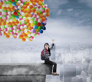 Student holding balloons on the rooftop Stock Photo