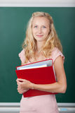 Student Holding Binder Against Chalkboard. Portrait of beautiful female student holding binder against chalkboard Royalty Free Stock Photo