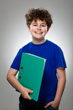 Student holding book. Standing against gray background Royalty Free Stock Image