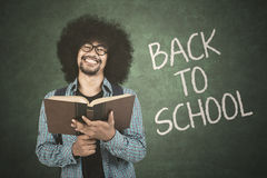 Student holding book with back to school text. Afro young student holding a textbook with back to school text on chalkboard in the classroom Stock Photos