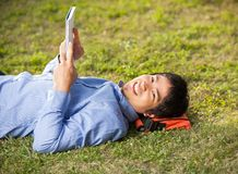 Student Holding Book While Lying On Grass At. Side view portrait of young male student holding book while lying on grass at university campus Stock Photography