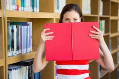 Student holding book over face Royalty Free Stock Photography