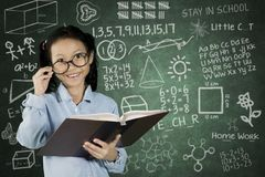 Student holding book with scribble on chalkboard Royalty Free Stock Photography