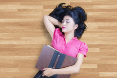 Student holding book and sleeping on the floor Stock Images