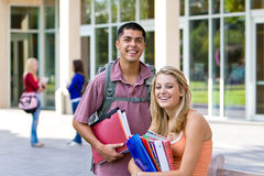Student Holding Books. Two young male and female students carrying their books outside of school. There are kids in the background. Horizontally framed photo Stock Photo