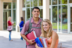 Student Holding Books. Two young male and female students carrying their books outside of school.  There are kids in the background. Horizontally framed photo Royalty Free Stock Images