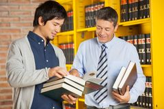 Student Holding Books While Discussing With. Happy male student holding books while discussing with librarian in college library Stock Images