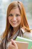 Student holding books in front of window Royalty Free Stock Images