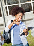 Student Holding Books While Gesturing Loser Sign Stock Image