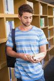 Student holding books in library. At the university Stock Photo