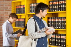 Student Holding Books While Looking At Shelf In. Male student holding books while looking at shelf in college library Stock Image