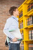Student Holding Books While Looking At Shelf In Stock Photography