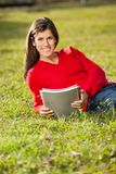 Student Holding Books While Relaxing On Grass At Royalty Free Stock Photo