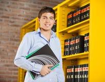 Student Holding Books Standing durch Regal in der Bibliothek Stockfotografie