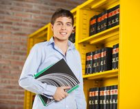 Student Holding Books Standing By Shelf In Library. Portrait of confident male student holding books standing by shelf in university library Stock Photography